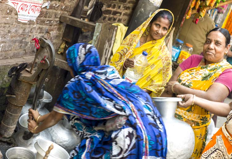 With running water a premium in many of the homes on Hindu Street, women take turns filling water jugs