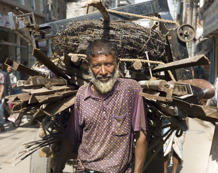Need to transport hundreds of pounds of barbed wire and building materials across town? Not much cash to get it there? Human labor's your cheapest option in Dhaka, where people compete with bikes, cars, trucks and animals for business.