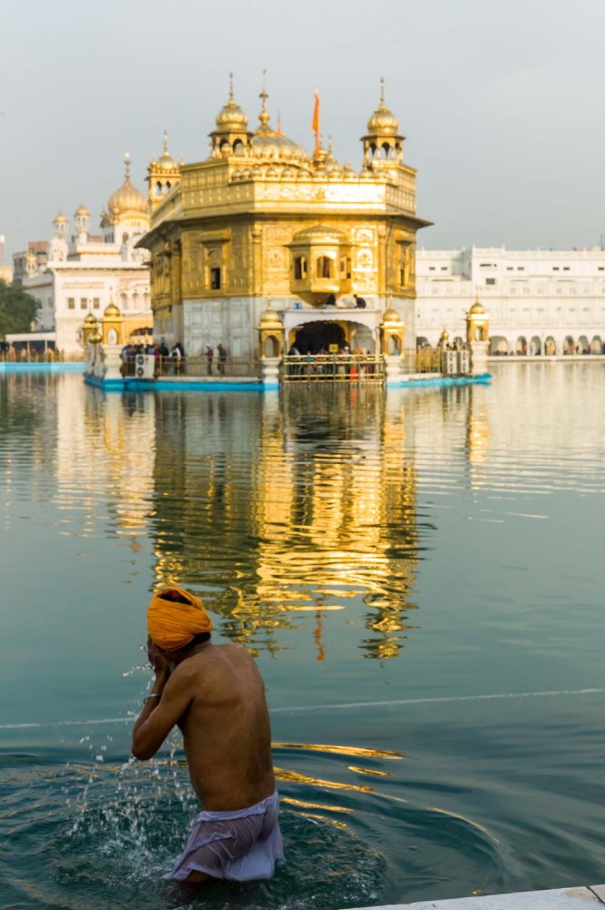 A pilgrim dipping in the holy pool surrounding the temple