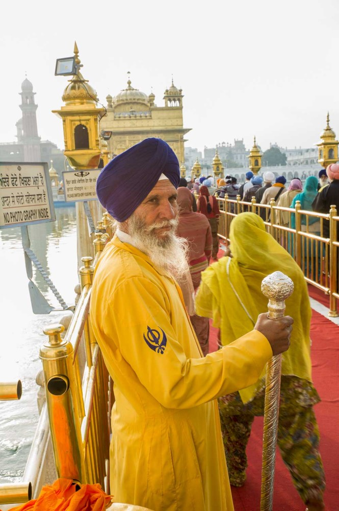 The symbol on the guards arm is the symbol of Sikhism, the Khanda. The Khanda represents divine knowledge, perfection of G-d the eternal, and the equal importance in Sikh life of spiritual aspirations and an obligation and to society.