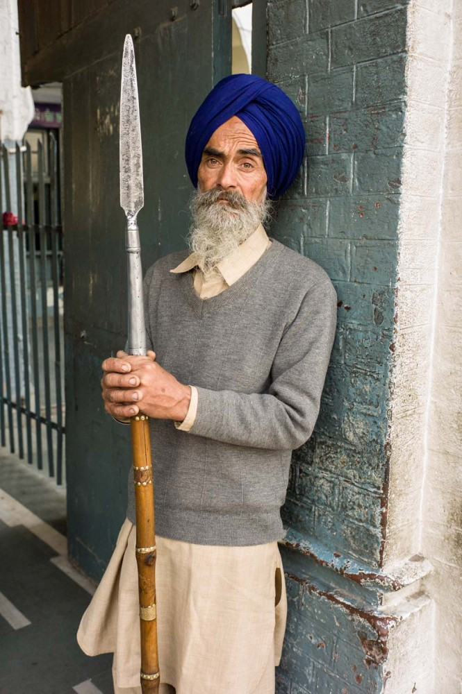 A guard standing watch outside of the Amritsar pilgrim lodgings