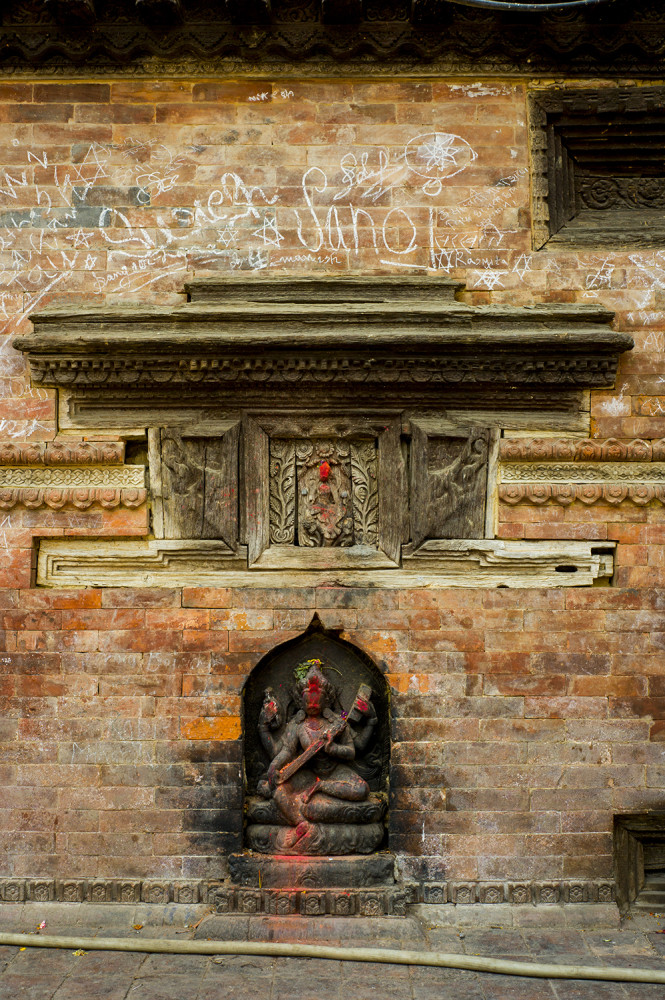 A shrine in central Kathmandu built into a graffiti-covered wall