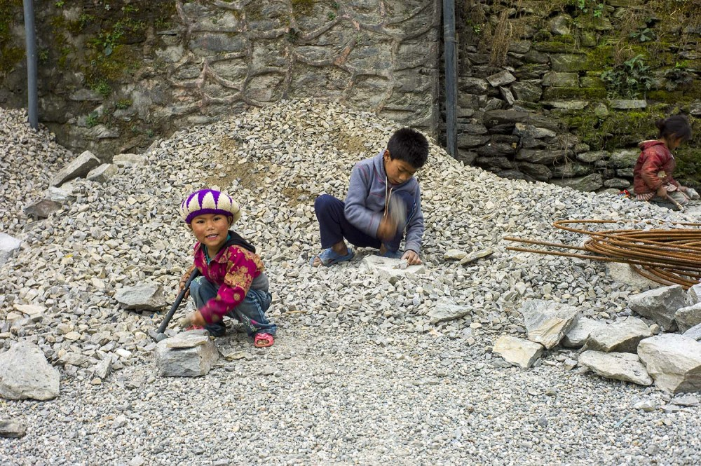 Cute children crushing rocks in Dunche