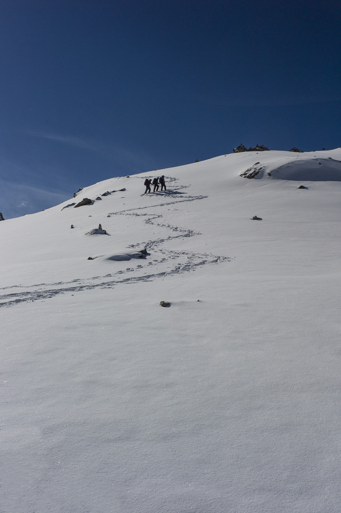 Hikers climbing up a snowy mountainside