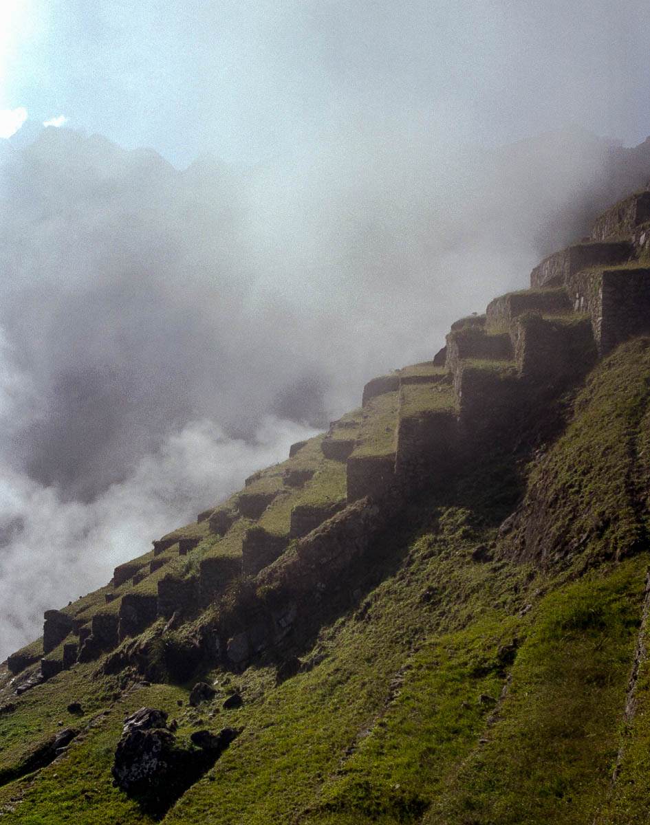 Clouds obscure the  surrounding terraced mountains around sunrise at Peru's Machu Pichu