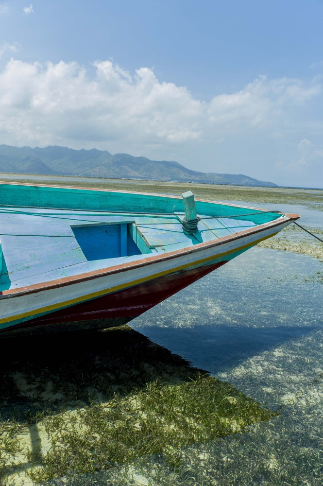 A tourist boat moored during low tide with Lombok, the next island in the chain in the distance