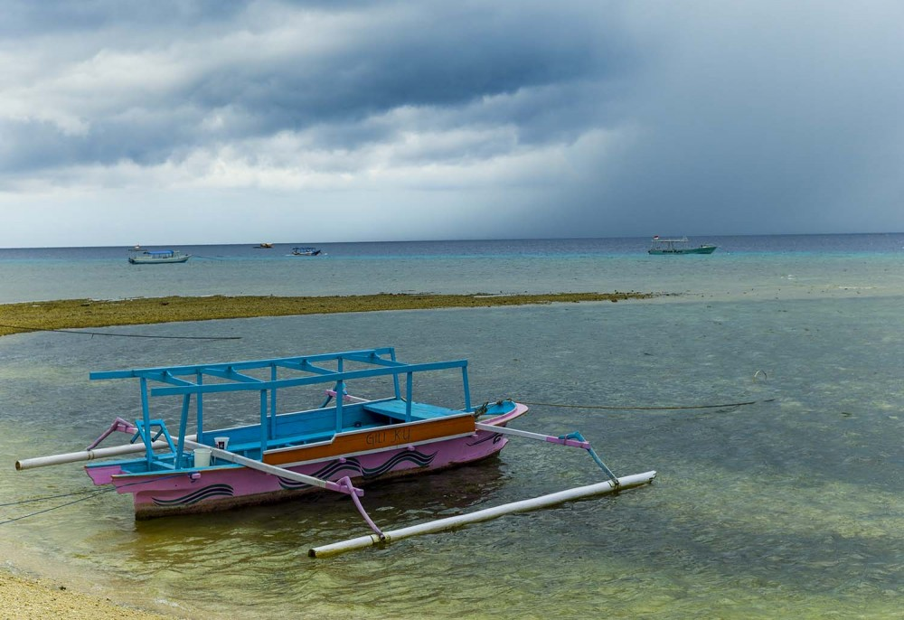 A glass bottom boat moored near the shore with an afternoon storm looming over the horizon