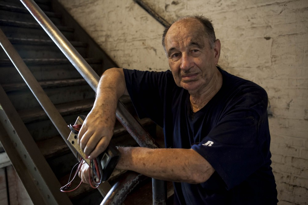 Edik Fishman climbing stairs to decommission the workshop's electrical system